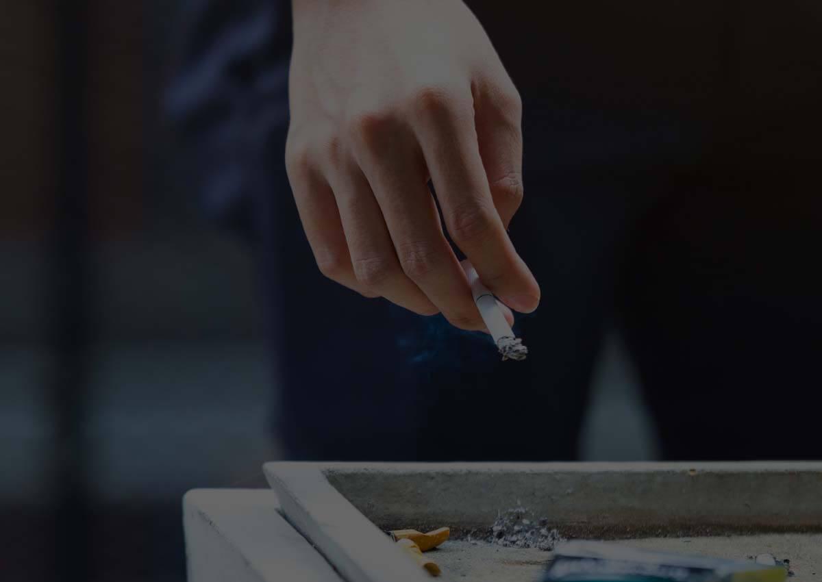 Fumeur avec une cigarette devant un cendrier extérieur